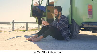 Young man texting on mobile phone near van 4k - Young man ...