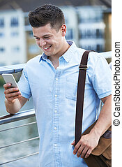 Young Man Texting On Mobile Phone Walking To Work