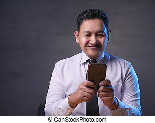 Young Man Texting Reading Chatting on His Phone, Smiling Happy