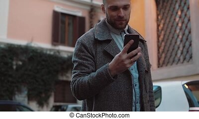 Young man texting sms, using app on smarphone in city. Handsome businessman using touchscreen technology, smiling.