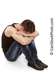 Young man thinking and hiding his face between his knees