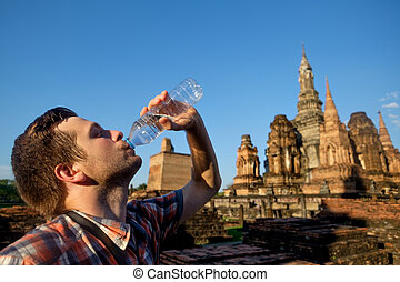 Young man thirsty is drinking bottled water in buddhism temple in Thailand