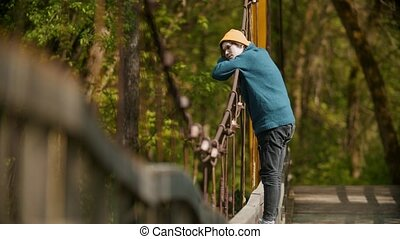 Young man thoughtful man standing on the bridge in the forest