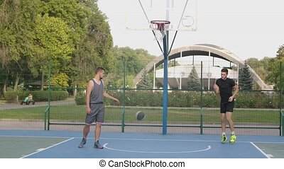 Young man throwing basketball ball in hoop on court in park ...