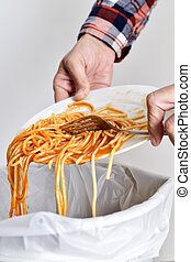 closeup of a young man throwing the leftover of a plate of spaghetti to the trash bin