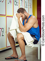 Young man tired in locker room sitting - Young adult fit man...