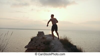 Young man topless standing on the edge of a cliff enjoying...