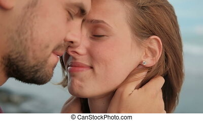 Young man touches face of woman and kisses standing on sea shore on summer evening.