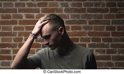 Young and handsome caucasian man touching his straight fair hair before the brick wall, isolated, slow motion