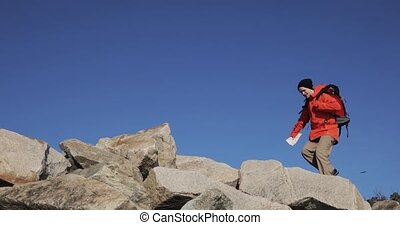 Young man tourist is hiking on the stones on mountain with map in his hand.