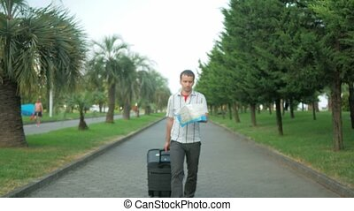 Young man tourist is with a large suitcase on wheels around the city park. In his hands map, and he's looking for the right road.