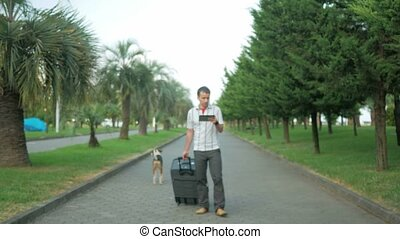 Young man tourist is with a large suitcase on wheels around the city park. In the hands of a tablet with a tablet and is looking for the right road. Nearby walks stray dog.