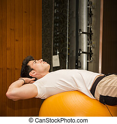 Young man training abs on fitness ball