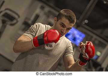 Young man training boxing in the gym