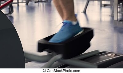 Young Man Training on Elliptical Machine in Gym