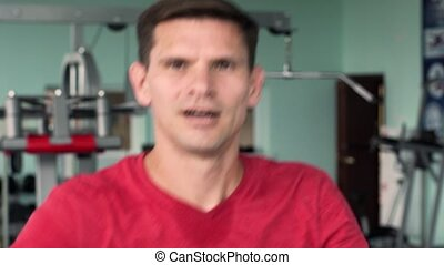 Young Man Training on Elliptical Machine in Gym