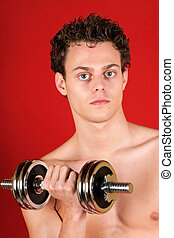 Young man training with dumbbell