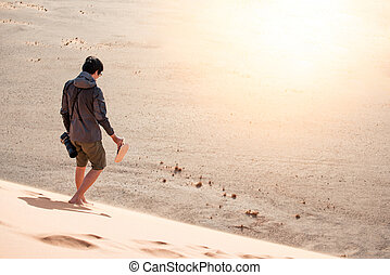 Young man traveler walking down the sand dune with bear foot