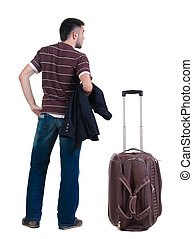 young man traveling with suitcas looks ahead. rear view.