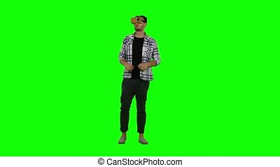 Young man trying virtual reality glasses - VR glasses - and exploring virtual reality. Green screen
