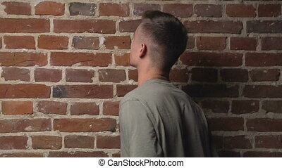 Young and handsome caucasian man turning around before the brick wall, isolated, slow motion