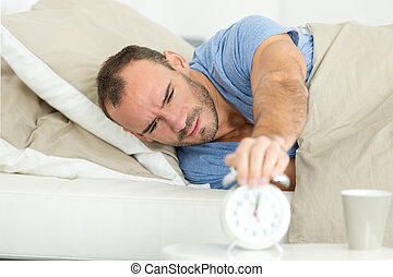young man turning off the alarm clock on the bed