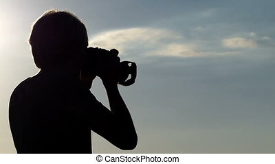 Young man turns and shoots a panorama at sunset