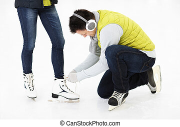 Young man tying skates on a skating rink