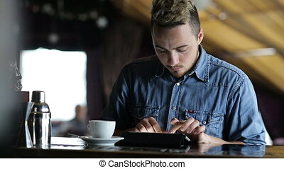 Young man typing on a tablet while sitting at the bar