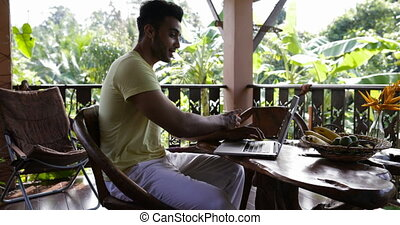 Young Man Typing On Laptop Computer Having Breakfast On...