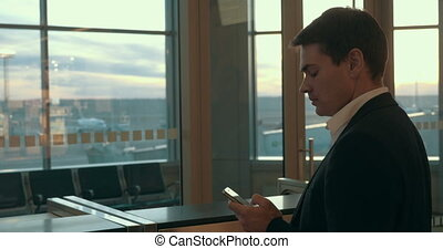 Young man typing sms in airport