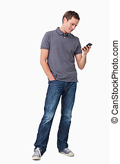 Young man typing text message on his cellphone against a...