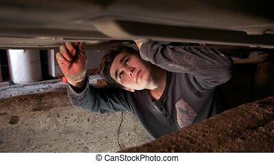 Young man underneath a car repairs his car in the garage pit