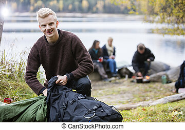 Young Man Unpacking Backpack At Campsite