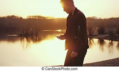 Young man uses smart phone and walks at beautiful sunset on the beach. slow motion.