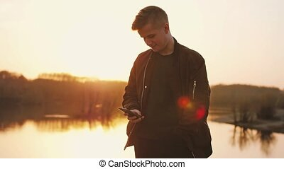 Young man uses smart phone at beautiful sunset on the beach. slow motion.