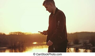 Young man uses smart phone at beautiful sunset walks on the beach. slow motion