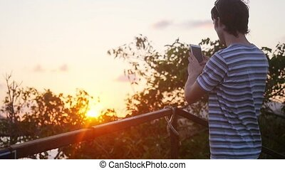 Young man using a cellphone on the mountain during beautiful sunset with lense flare effects in slow motion.