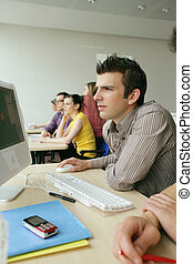 Young man using a computer in class