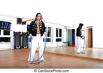 .young man using a jump rope