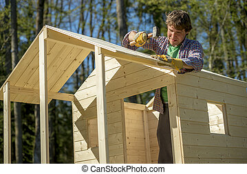 Young man using a mallet to fix a nail into a roof of a wooden playhouse