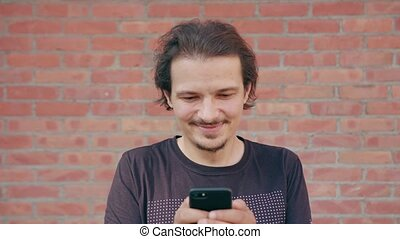 Young Man Using a Phone against a Brick Wall Background - An...
