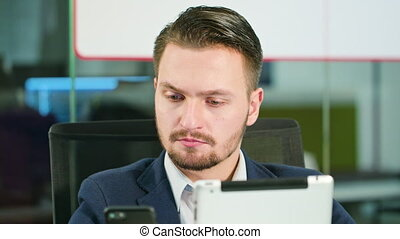 Young Man Using a Phone and a Tablet in the Office