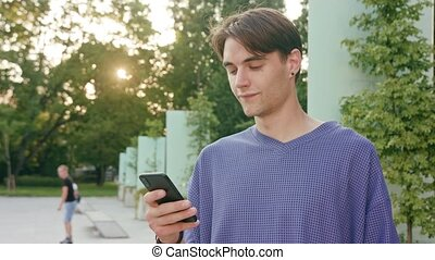 Young Man Using a Phone in Town