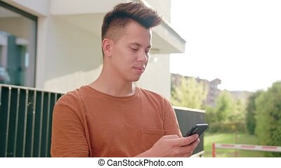 Young Man Using a Phone in Town - An attractive young man...