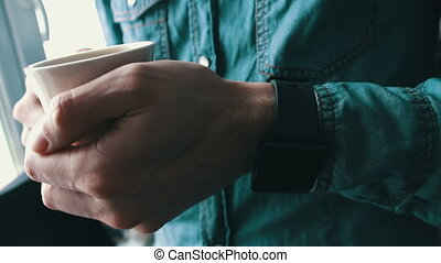 Young man using a smart watch holding white cup of coffee