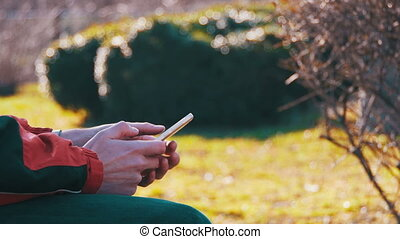 Young Man using a Smartphone on a Bench in the City Park