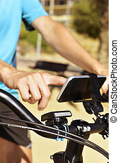 young man using a smartphone riding a bicycle