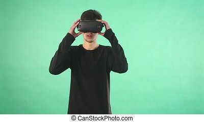 Young man using a virtual glasses against green background