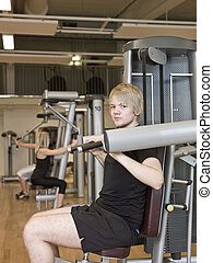 Young man using an exercise machine